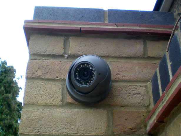 CCTV camera installed on a brick gate pier